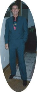 Len Millman, founder of Celebration Ostomy Support Belt, standing in a blue suit